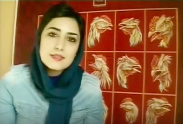 A photo of Iranian cartoonist Atena Farghadani in front of one of her paintings